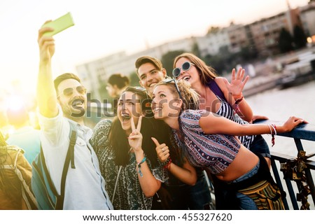 Shutterstock Happy young people taking selfies in city