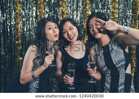 Happy young people with cocktails at pub taking picture face camera smiling. crazy lovely girls kissing pose victory finger sign blinking eyes. group of asian women having fun photographing at club.