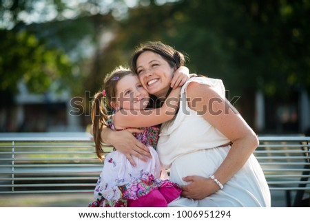 Happy young pregnant mother embracing her affectionate daughter. #1006951294