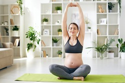 Happy young pregnant woman in activewear keeping her hands put together while raising stretched arms during yoga exercise