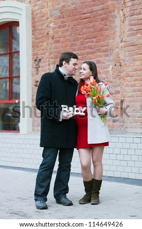 Happy young pregnant woman with her husband outdoors