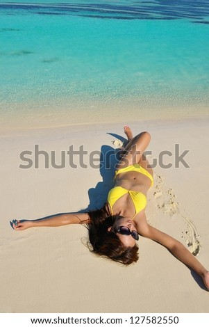 happy young pretty asian woman resting on sand at beach - stock photo