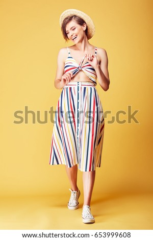 Happy young pretty woman with short hair wearing colored summer dress, straw hat and white shoes posing in studio on yellow background #653999608