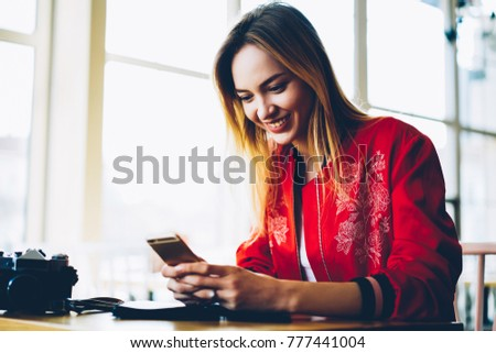 Happy young professional photographer installing new photo application on modern telephone device.Positive female blogger uploading pictures and videos on own web page via high speed internet #777441004