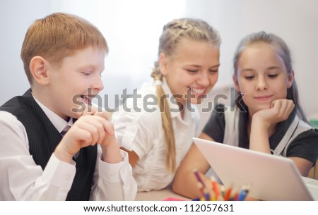 Happy young pupils sitting at the table and chatting during studying