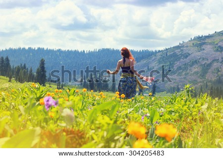 Happy young red hair woman running and dancing on the flowers field into the mountains. Happy travel concept. Mountain trekking. Woman in harmony with nature.