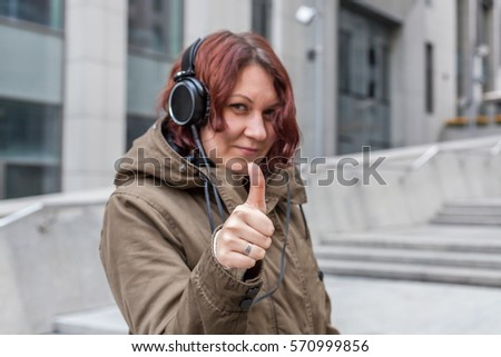 Happy young red-haired woman with big headphones shows thumb up #570999856