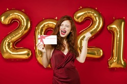 Happy young redhead woman in elegant dress hold gift certificate doing winner gesture isolated on red background, golden numbers air balloons. Happy New Year 2021 celebration holiday party concept