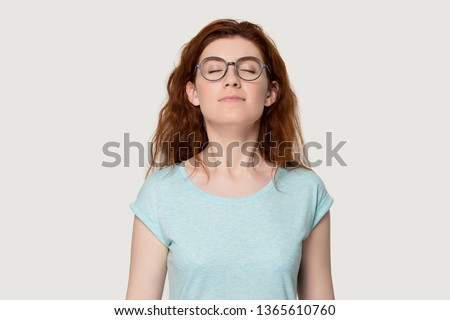 Happy young redhead woman in glasses feel calm breathe fresh air managing stress practicing exercises, peaceful red-haired girl in eyewear isolated on grey background smell inhale pleasant fragrance