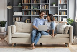 Happy young relaxed couple sitting on sofa with laptop on laps, discussing funny movie, enjoying watching comedian film, shopping online or web surfing, full length front view, leisure pastime concept