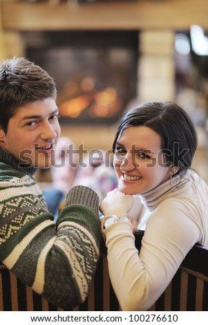 happy Young romantic couple and relaxing sofa in front of fireplace at winter season in home - stock photo
