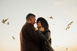 Happy young romantic couple hugging and looks at each other with love. Young couple sharing happy and love mood on the beach with flying seagulls on background.