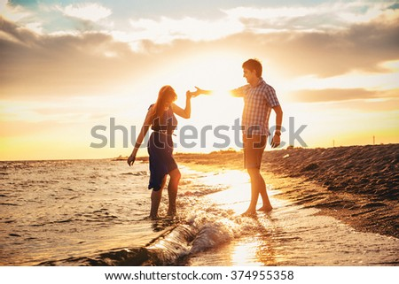 happy young romantic couple in love have fun on beautiful beach at beautiful summer day #374955358