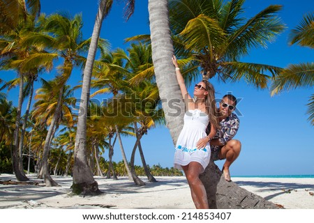 Happy young romantic couple in love relaxing on luxury private Caribbean beach under palm tree