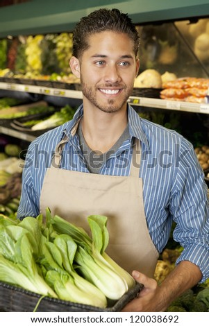 Happy young sales clerk holding bok choy in supermarket