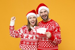 Happy young Santa couple friends man woman in red sweater Christmas hat hold gift certificate doing winner gesture isolated on yellow background. Happy New Year celebration merry holiday concept