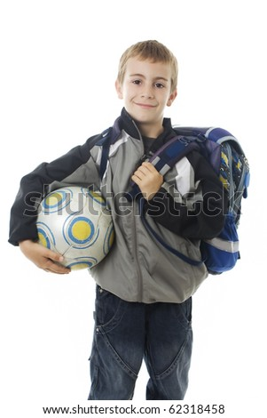 Happy young school boy holding a football ball isolated on white