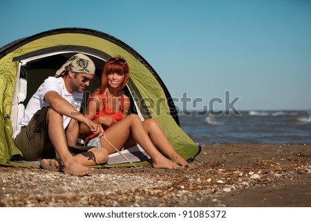 happy young sitting in a tent by the sea, talking, enjoying the summer sun