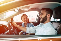 Happy young smiling couple riding in car on the road. Handsome bearded man is sitting at the wheel.