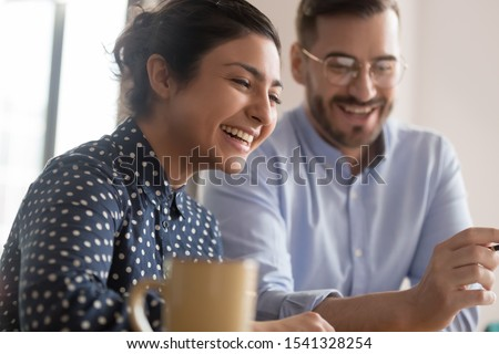 Happy young smiling diverse couple of female indian and male caucasian coworkers watching funny videos during coffee break, getting positive news, making good deal, holding video call with client