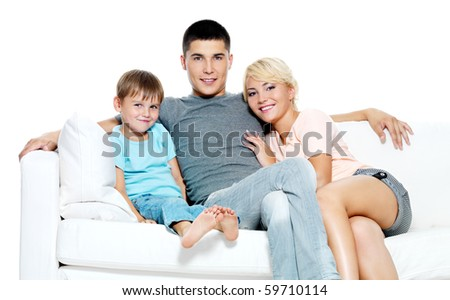 Happy young smiling family with kid sitting on white sofa - Isolated