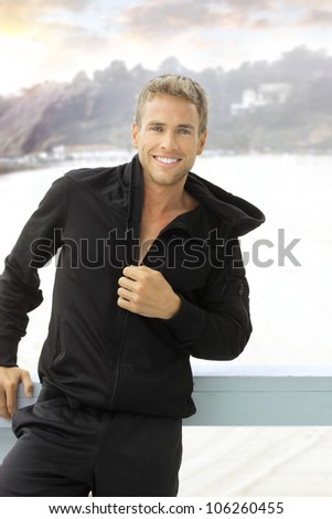 Happy young smiling man outdoors - stock photo