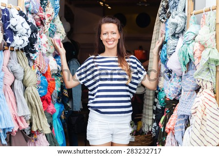 Happy, young, smiling woman standing at the clothes store entrance, looking at camera
