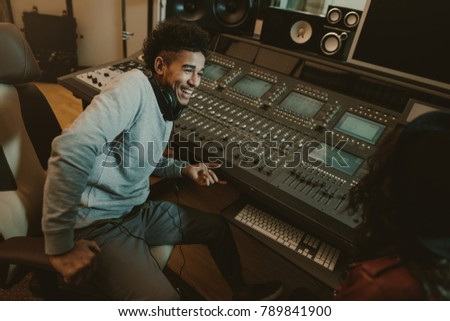 happy young sound producer sitting at studio #789841900