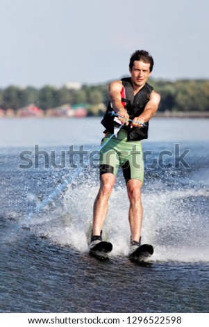 Happy Young sportive teenage boy waterskiing from the boat. Adventurous summer holidays at the sea. Water sport activity on the beach. #1296522598
