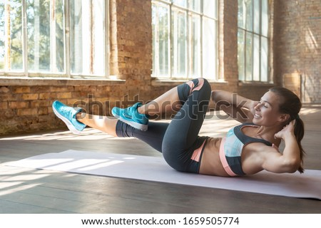 Happy young sporty girl woman fitness trainer do bend knee to elbow crunch abdominal weightloss bicycle exercise burn calories mat stretch modern gym wooden floor healthy lifestyle concept copy space.