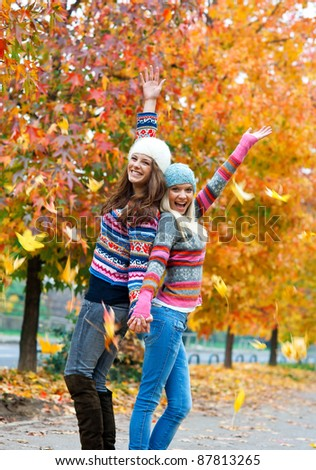 happy young teen girls in autumn scenery throwing leaves - stock photo