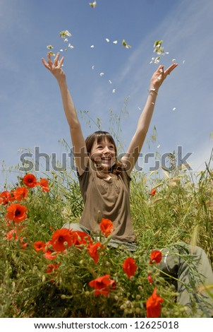 happy young teenager in a field of spring flowers