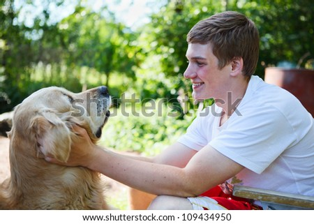 Happy young teenager with golden retriever dog together embracing