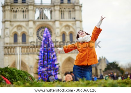 Happy young tourist in Paris on a winter day, main Parisian Christmas tree and Notre-Dame cathedral in the background #306360128