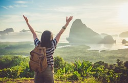 Happy young traveler woman backpacker raised arm up to sky enjoying a beautiful of nature at top of mountain and sea view,Freedom wanderlust concept