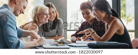 Happy young university students studying with books in library. Group of multiracial people in college library.