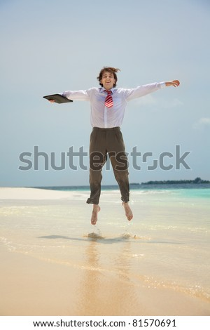 Happy young white-collar worker jumping on the shore of the sea