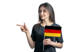 Happy young white woman holding flag Germany and points to the left isolated on a white background.