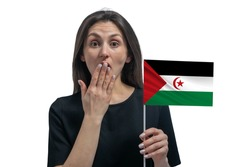 Happy young white woman holding flag of Western Sahara and covers her mouth with her hand isolated on a white background.