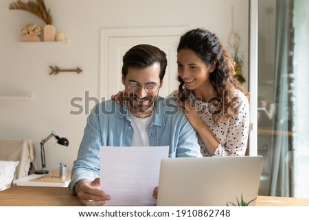 Happy young wife embrace shoulders of beloved husband reading official paper letter of getting job promotion loan mortgage approval. Glad married couple impressed with perfect news received by mail