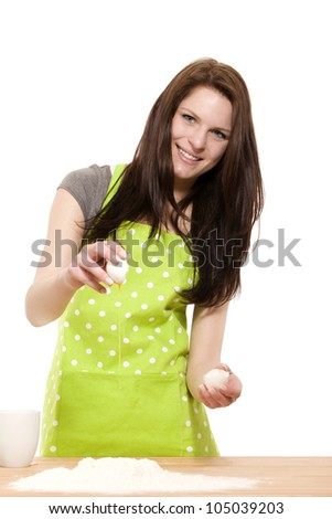 happy young woman adding an egg to flour for baking on white background