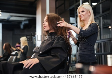 Happy young woman and hairdresser with fan making hot styling at hair salon