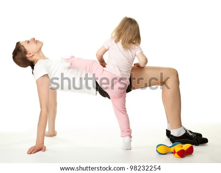 Happy young woman and her little daughter doing sport exercises together; white background