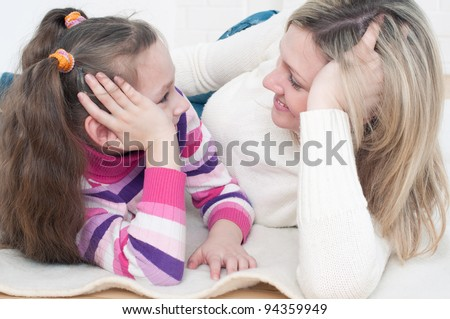 Happy young woman and her little daughter lying on the floor and looking at each other