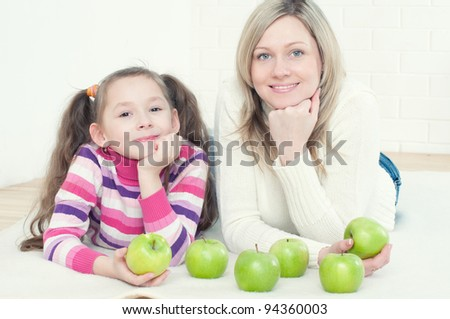 Happy young woman and her little daughter lying on the floor with green apples
