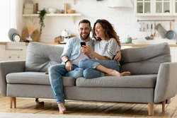 Happy young woman and man hugging, using smartphone together, sitting on cozy couch at home, smiling overjoyed wife and husband looking at phone screen, sitting on sofa in modern living room