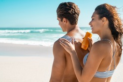 Happy young woman applying suntan lotion on boyfriend back at beach. Wife applying sunscreen lotion on man back at beach in sunshine. Girl put protection uv cream on shoulder of guy with copy space.