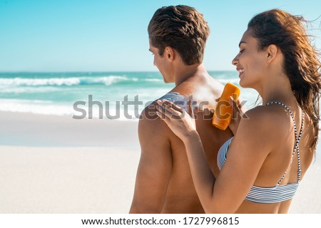 Happy young woman applying suntan lotion on boyfriend back at beach. Wife applying sunscreen lotion on man back at beach in sunshine. Girl put protection uv cream on shoulder of guy with copy space. Stock photo ©