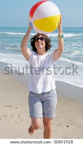 Happy young woman at the beach catching a ball