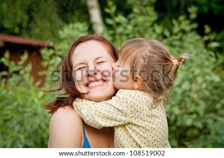 Happy young woman being kissed by a cute little girl